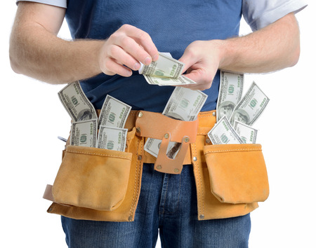 Concept of making money in the construction building trade,  a man counting money isolated on a white background photo