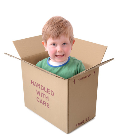 young boy in handle with care box isolated on a white background, concept of nanny state over protective parents.  photo