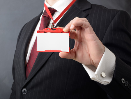 man in suit showing id or name badge  photo