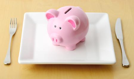 cuenta bancaria: Hucha en el plato con tenedor y cuchillo