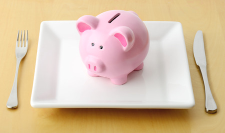 Piggy bank on the plate with fork and knife