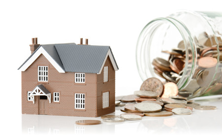 Concept for cost of living or housing a model house with coins