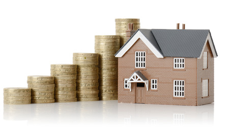 Concept of property value, house and coins isolated on a white background Stock Photo