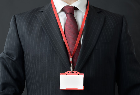 id card: man in suit showing id or name badge