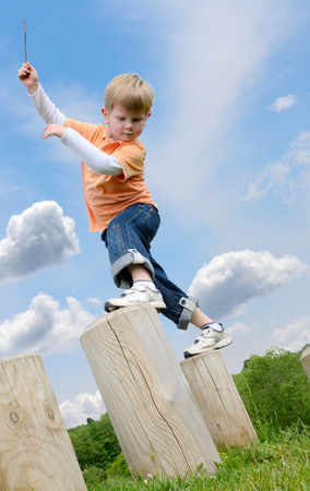 aciculum: young boy learning to balance on stepping posts Stock Photo