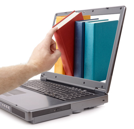 a hand taking out a book online, concept for e-learning or library photo