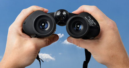 hands holding binoculars looking through from POV at blue sky