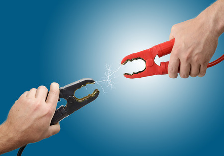 Hands holding jump start connectors with sparks between Stock Photo