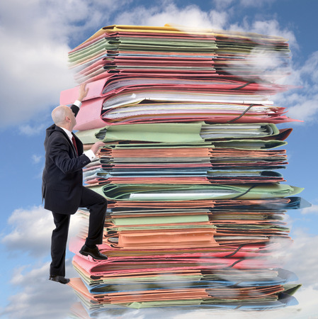 overflowing: businessman climbing pile of endless paperwork (digital composit) Stock Photo