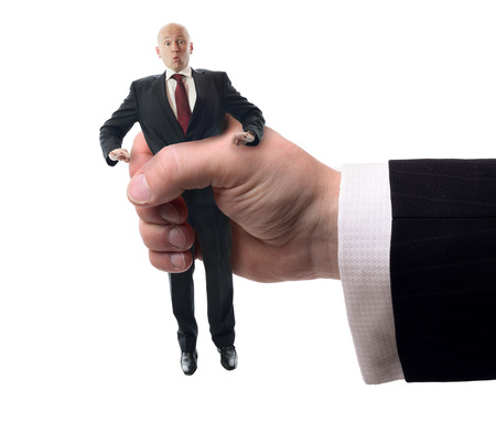 office politics: Businessman being squashed in a hand isolaed on a white background, concept of problems at work.