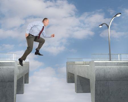 businessman jumping: A businessman jumping the gap on a bridge Stock Photo