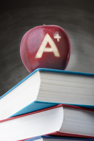 a red apple with an  A plus carved on it upon a stack of books, concept of top score photo