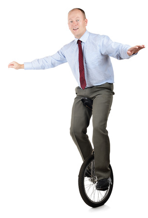 A businessman in a unicycle demonstrating skill and performance photo