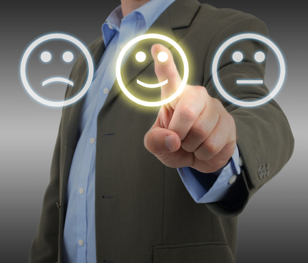 uomo felice: L'uomo in tuta la scelta di una faccina sorridente su un pannello sondaggio