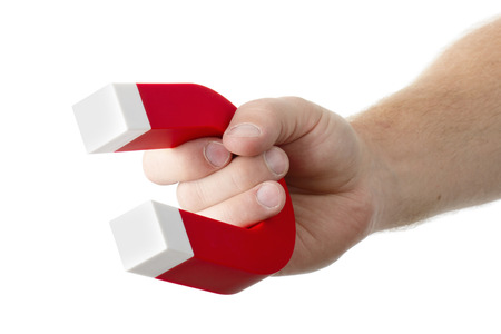 concept images: A hand holding a magnet isolated on white to pick up an object