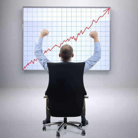 sales report: Businessman in office sat on a chair with arms raised in front of a successful growth chart Stock Photo