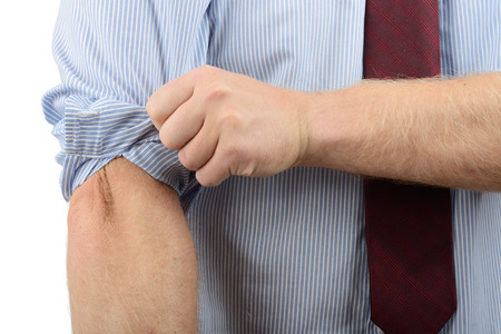 his shirt sleeves: Man in a shirt getting ready to do some work by rolling up his sleeves Stock Photo