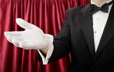 Person in a tuxedo and white gloves presenting or showing
