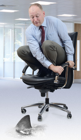 Concept of the competition circling a businessman scared on an office chair photo