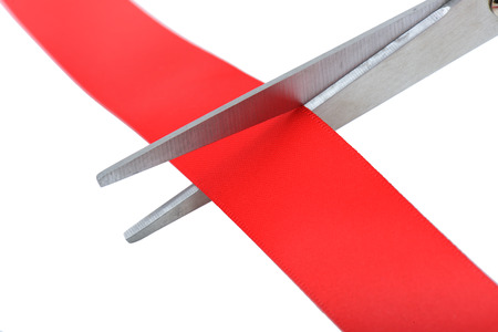 Closeup image of scissors cutting a red ribbon. Stock Photo