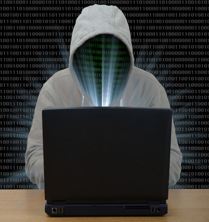 hooded shirt: Hacker typing on a laptop with binary code in background