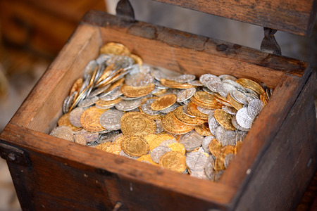 silver coins: Old wooden treasure chest full of coins Stock Photo