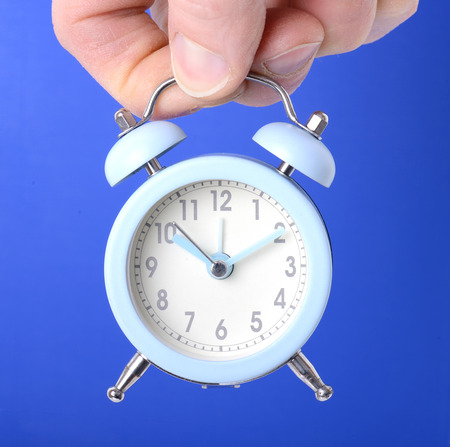 holding a small clock over a blue background photo