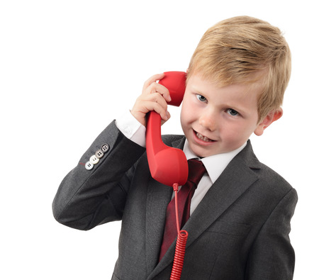 important phone call: young boy in a suit talking on a red phone isolated on a white background Stock Photo