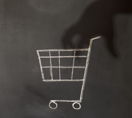 id theft: shadow of a hand reaching in to a shopping cart