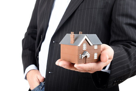 bargain: Close up of hands with little home. Concept of deal and real estate