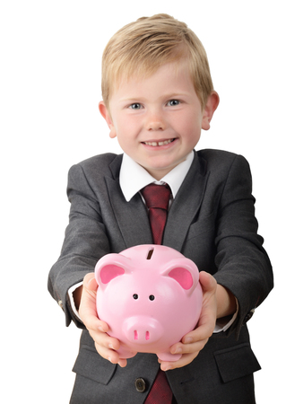 pennypinching: Young boy in business suit holding out a piggybank isolated on a white background focus on the piggy bank. Stock Photo