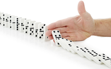toppled: hand stop dominoes continuous toppled Stock Photo