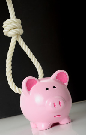 finacial: Concept of finacial problems a piggybank with a looming noose in the background
