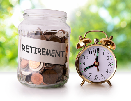 Coins in glass jar for retirement with retro alarm clock Stock Photo