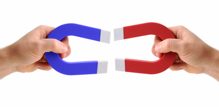 hands holding magnets one red and one blue isolated on a white background Stok Fotoğraf