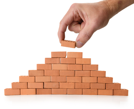 Concept of building and construction, a hand placing a brick on a wall, isolated on a white background