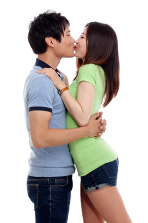 Happy couple hugging and kissing over white background photo