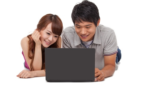 Happy couple using laptop isolated on white background