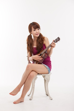 acoustic ukulele: Young Asian woman playing ukulele isolated on white background