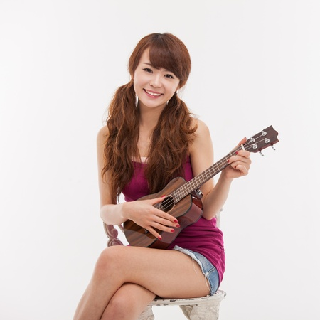 Young Asian woman playing ukulele isolated on white background  photo