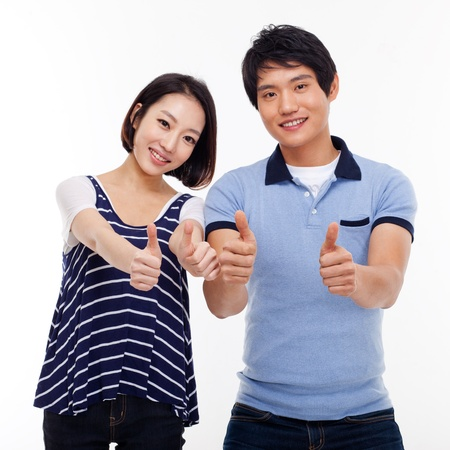 Young Asian couple show thumbs isolated on white background