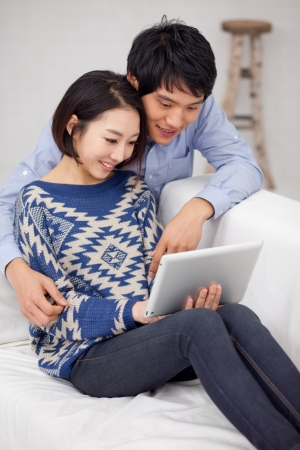 Young Asian couple using pad PC Stock Photo - 17184659