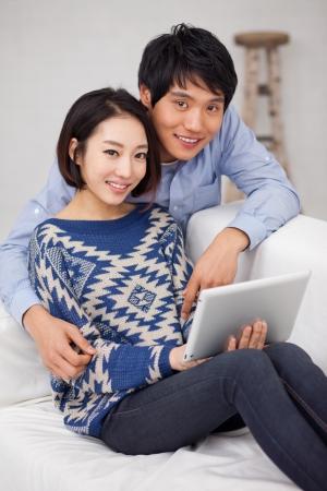 pareja en casa: Pareja asi�tica joven que usa PC pad Foto de archivo