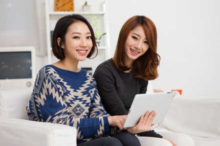 Two Asian young woman using tablet PC  photo