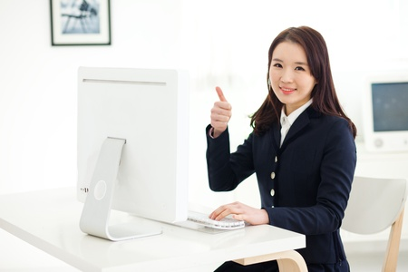 Happy Asian young woman using computer in home background.