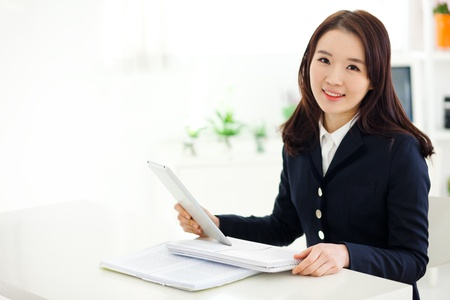 Young Asian student studying with pad PC in home background.  Stock Photo