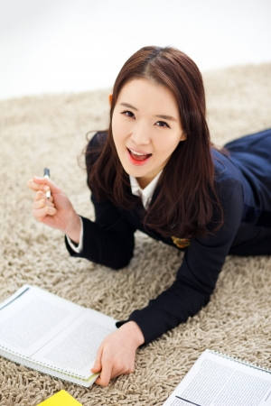 english girl: Yong pretty Asian student studying  with lying down.  Stock Photo