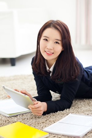 Yong pretty Asian student studying  with tablet PC.  photo