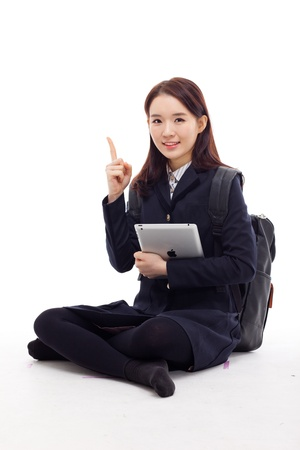 Yong pretty Asian student studying  with tablet PC isolated on white background   photo