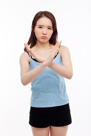 to restrain: Young Asian woman show prohibit sign isolated on white background.